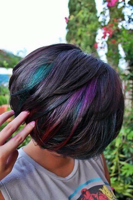 a short black bob with purple, teal and red peekaboo highlights that make it super bold