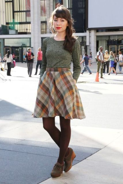 a green printed long sleeve top, a colorful plaid A-line skirt and neutral wedges