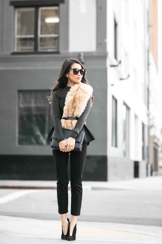a grey peplum top, black cropped pants, a black clutch and a faux fur scarf with a belt
