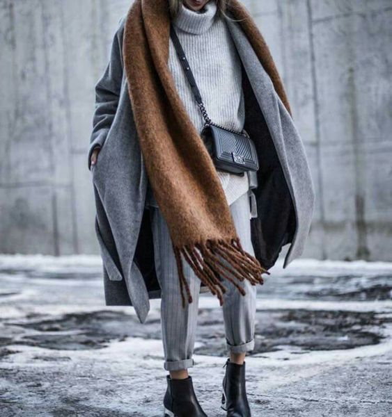 an oversized grey sweater, grey pants, a grey coat, black booties and a large brown scarf