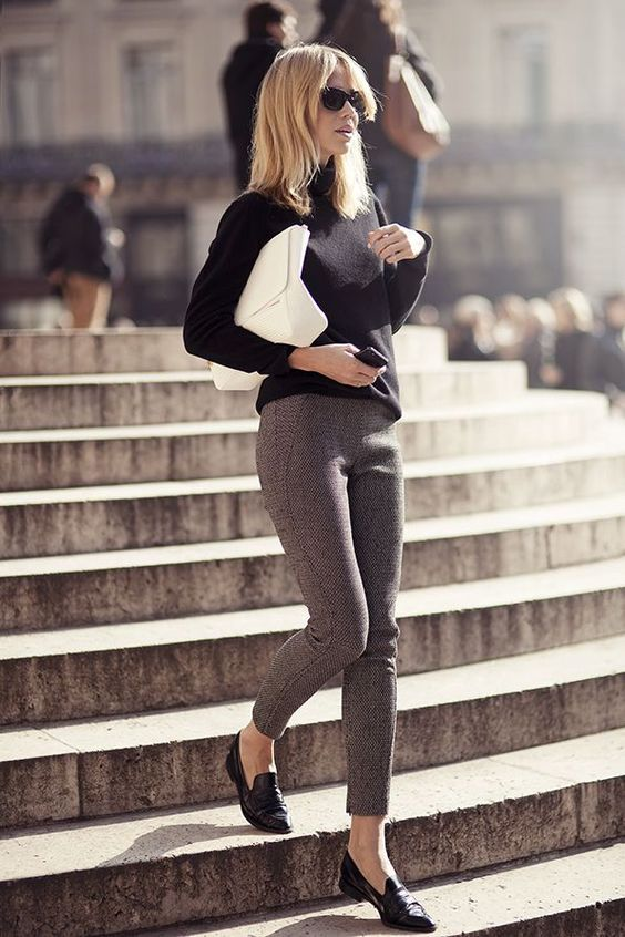 grey cropped pants, black loafers, a black turtleneck and a white clutch for a minimalist work look