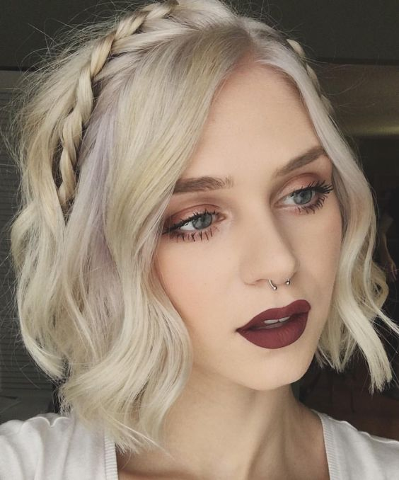 a blonde wavy bob with pastel touches and two braids, on on each side