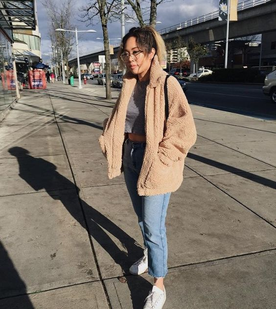 a grey tee, a fuzzy faux fur coat, blue cropped jeans, white sneakers for a cold fall day