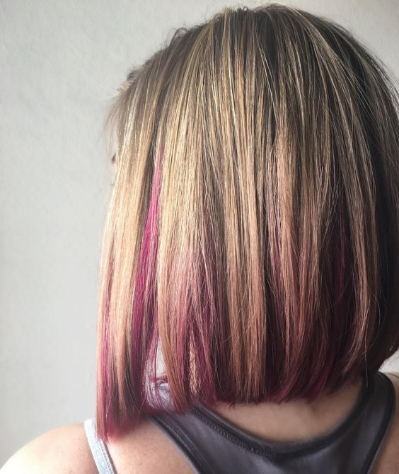 a long blonde bob wth pink peekaboo highlights that make usual blonde stand out