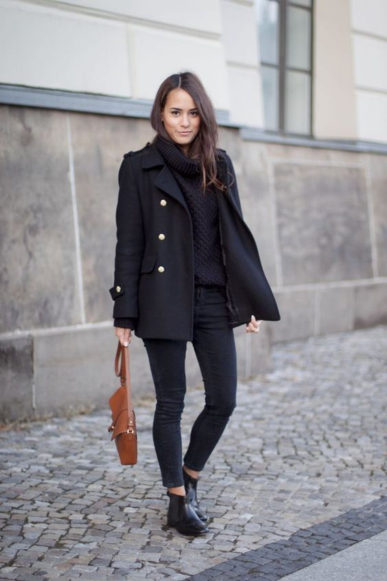 black cropped skinnies, a black cowl sweater, a short black coat with gold buttons and a brown bag