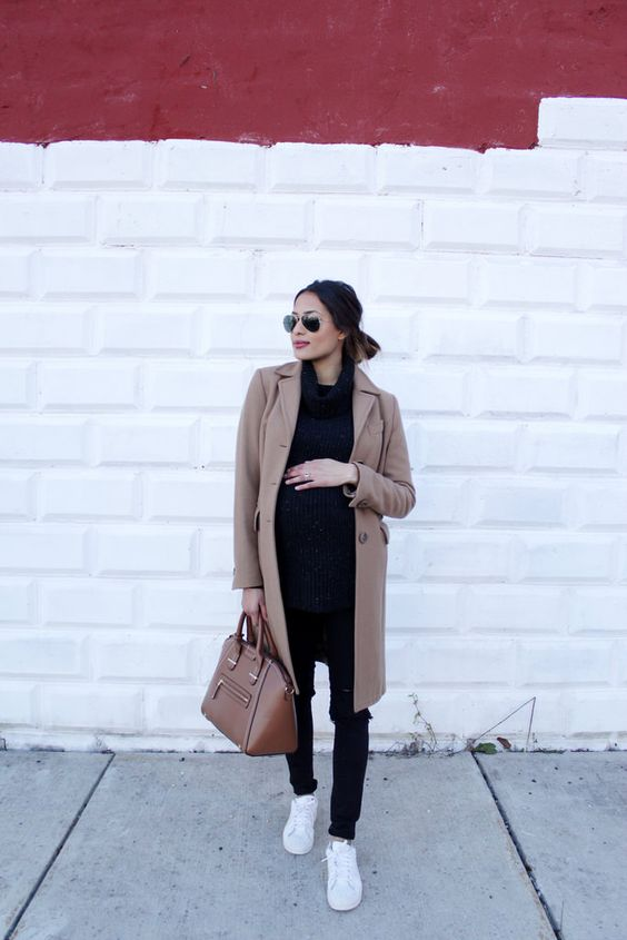 black ripped skinnies, a black cowl sweater, a camel coat, white sneakers and a brown bag