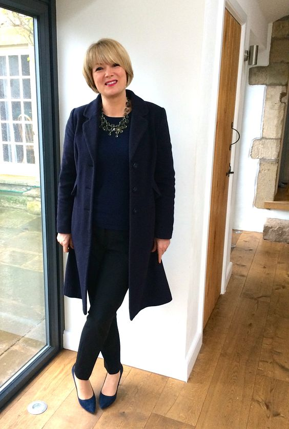 black skinnies, a navy top, a blue coat, navy suede heels, a statement necklace and a bold lip