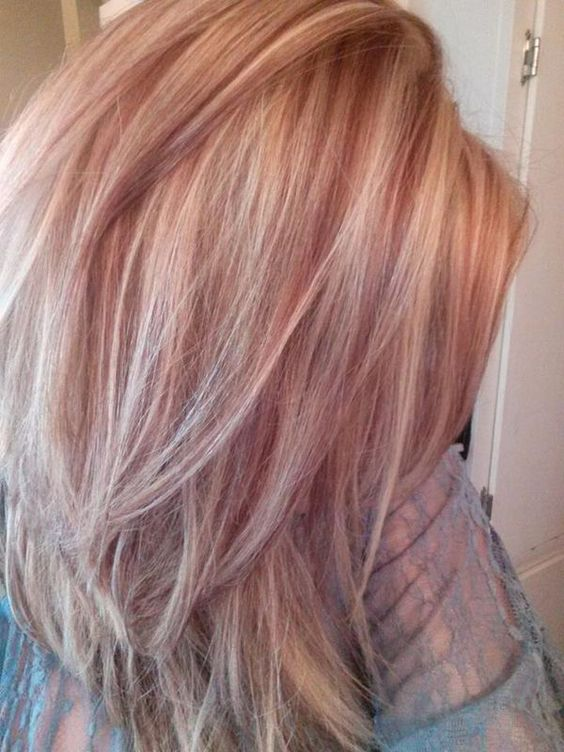 blonde medium length hair with strawberry blonde highlights and a slight cascade for a chic look
