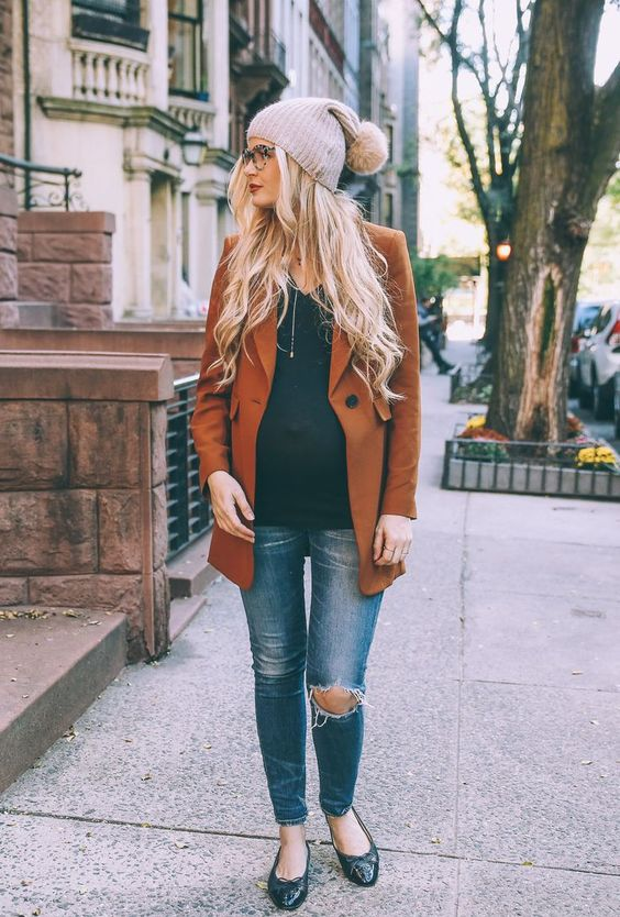 a black top, blue ripped skinnies, a rust blazer, black flats and a pompom hat