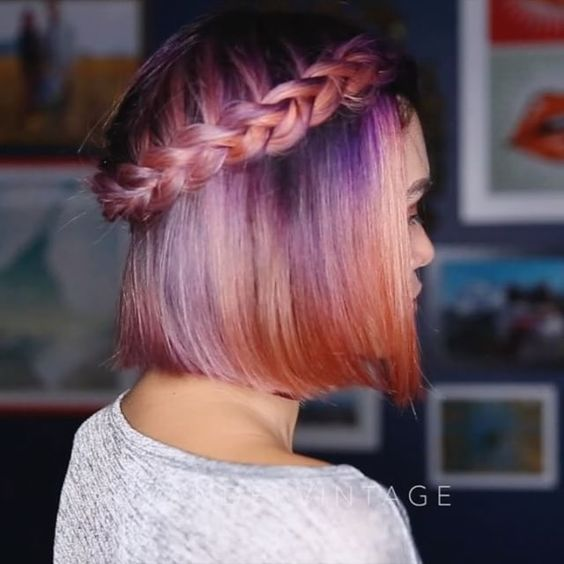 a bright purple to orange ombre bob and a waterfall braid for a boho feel