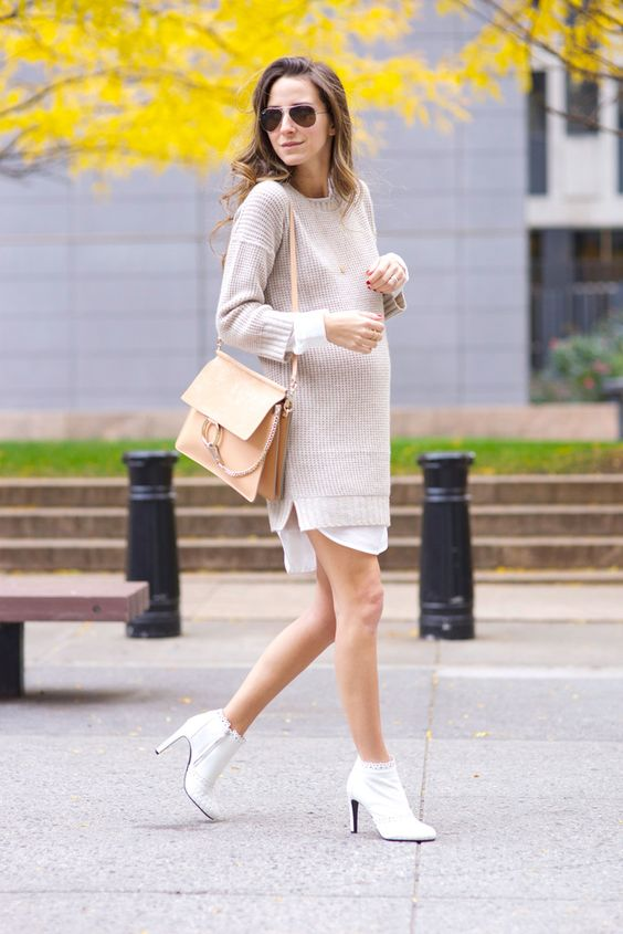 a long shirt, a neutral oversized sweater, white booties and a beige bag for a casual work look