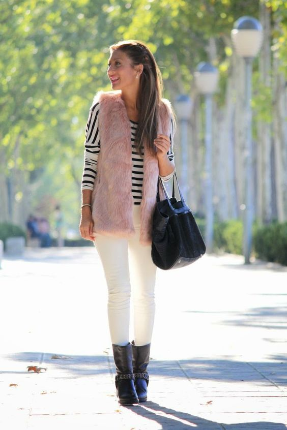 a striped long sleeve top, white jeans, a pink faux fur waistcoat, black boots and a bag