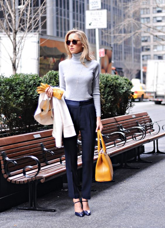 black pants, a grey turtleneck, navy heels and a mustard bag for look with bright fall touches