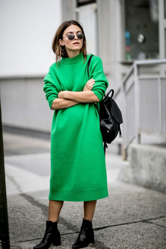 a bold green knit midi dress with a high neckline, black booties and a bag to make a statement