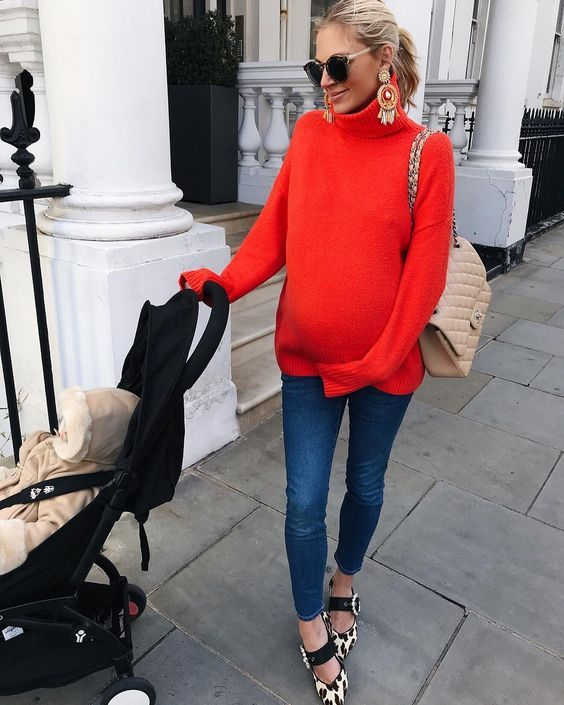 maternity look in a bright orange sweater, blue skinnies, printed flat shoes and a beige bag