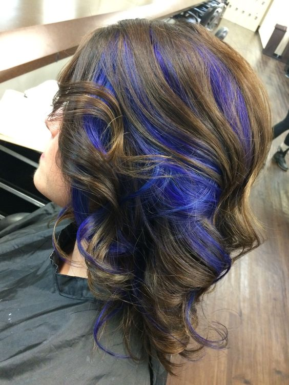 chestnut wavy hair with purple peekaboo highlights for a super bold look
