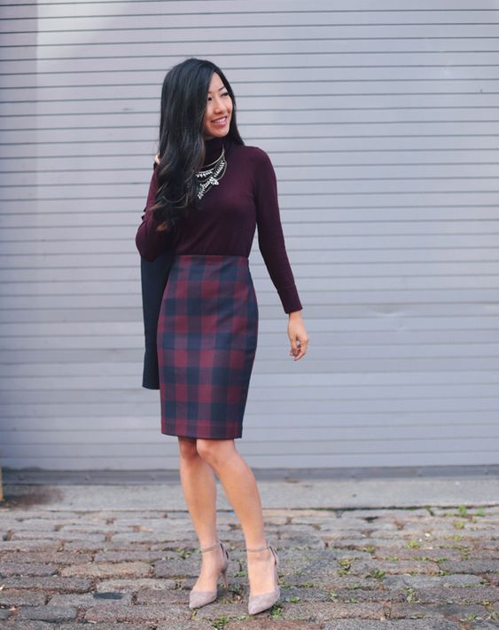 a buffalo check knee skirt, a plum-colored turtleneck, blush suede shoes and layered necklaces