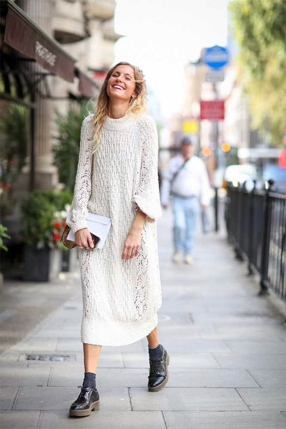 a chic white sweater midi dress, black flat shoes and a white clutch for winter comfort