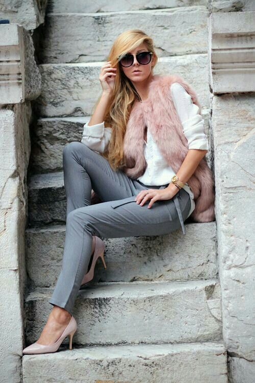 a white long sleeve tee, grey pants, nude heels and a pink faux fur vest for a bright look