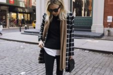 11 black skinnies plus boots, a white shirt, a black sweater, a plaid coat and a neutral scarf