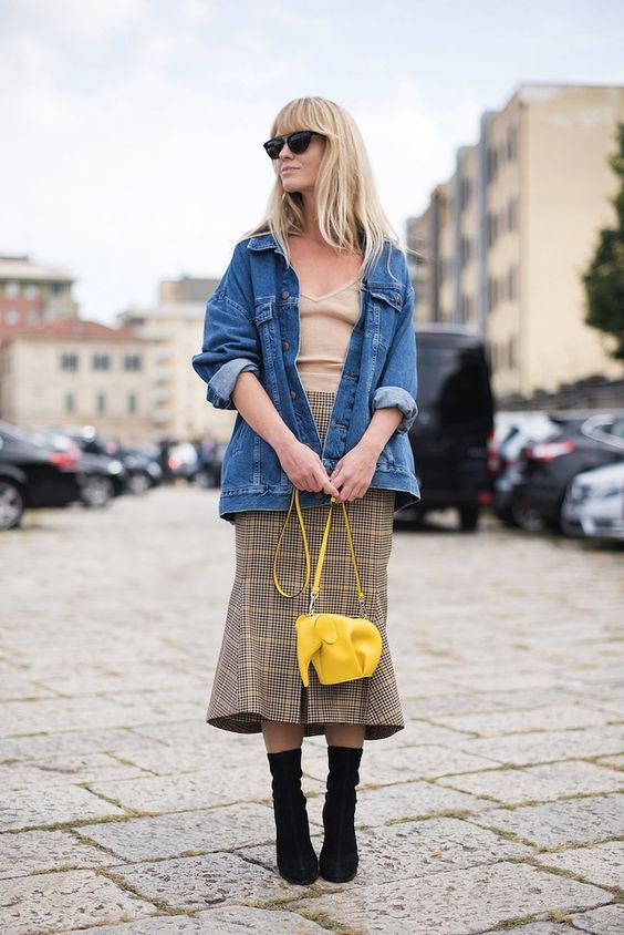 a neutral top, a plaid midi skirt, black sock boots, a denim jacket and a bright yellow bag