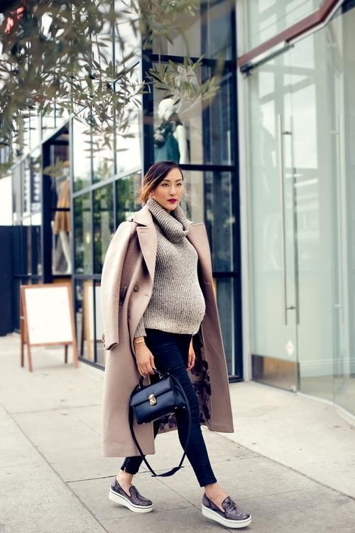 navy skinnies, a grey cowl sweater, platform shoes, a camel coat and a small bag