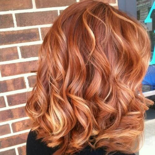 red wavy hair with strawberry blonde highlights is a chic and bright idea for standing out