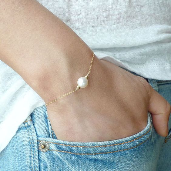 rock denim, a teee and a bracelet with a single pearl for an effrtlessly chic look