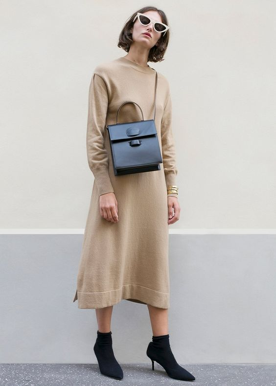 a midi knit beige dress, black sock boots, a black bag and trendy sunglasses