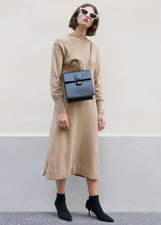 a midi knit beige dress, black sock boots, a black bag and trendy sunglasses