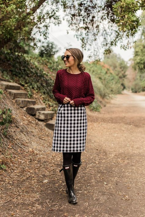 a plum-colored sweater, a plaid skirt, black tights and black rubber boots for outdoor walks