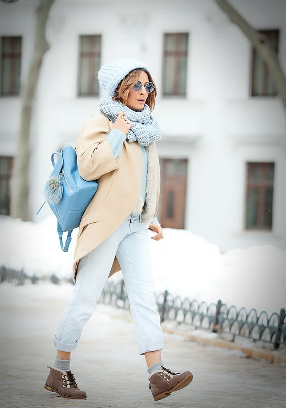 a powder blue sweater and pants, a light yellow coat, a powder blue scarf and beanie, a blue backpack