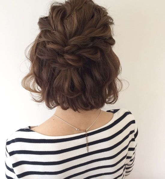 a short curly bob with two double braids on top looks very relaxed and cute