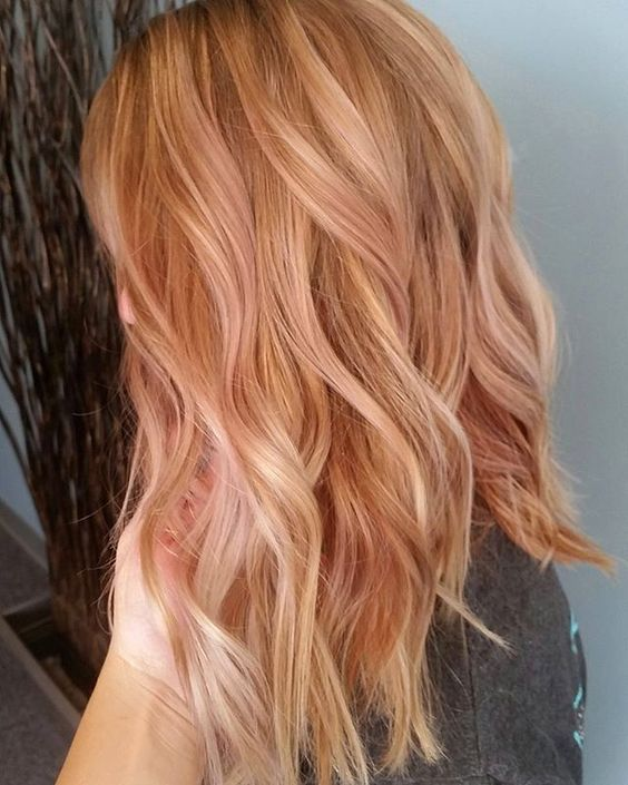 rose gold wavy hair with strawberry blonde highlights are a chic and very girlish idea