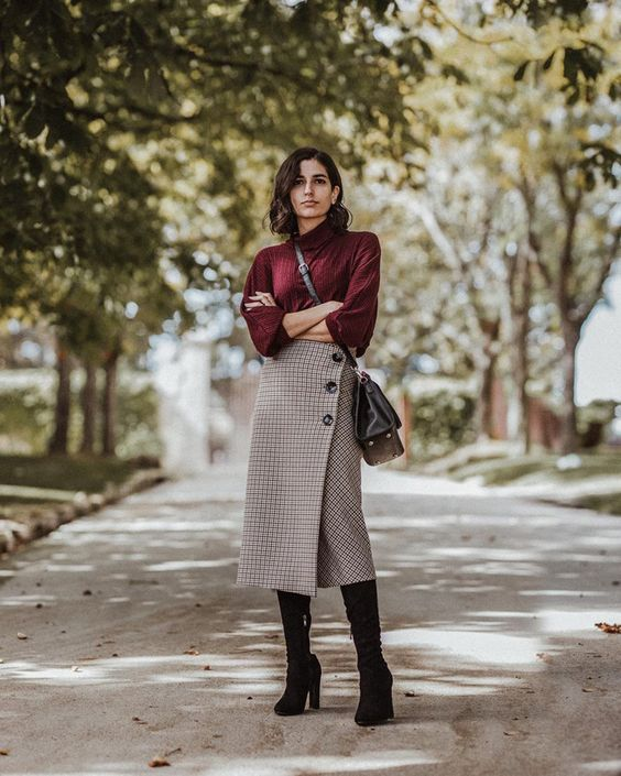 a plum-colored turtleneck, a plaid pencil midi skirt with buttons, black boots and a black bag