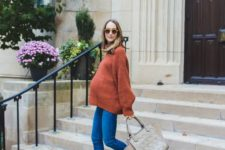 14 blue skinnies, an oversized rust sweater, electric blue booties and a grey bag for a casual Thanksgiving look