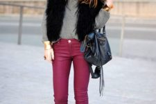 14 fuchsia jeans, a grey sweater, a black fuax fur vest, black booties and a navy bag
