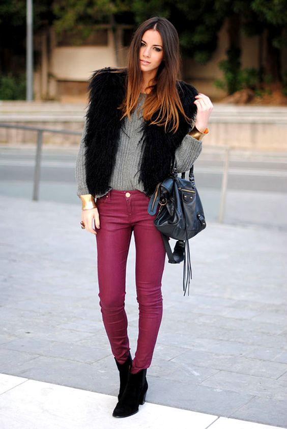 fuchsia jeans, a grey sweater, a black fuax fur vest, black booties and a navy bag