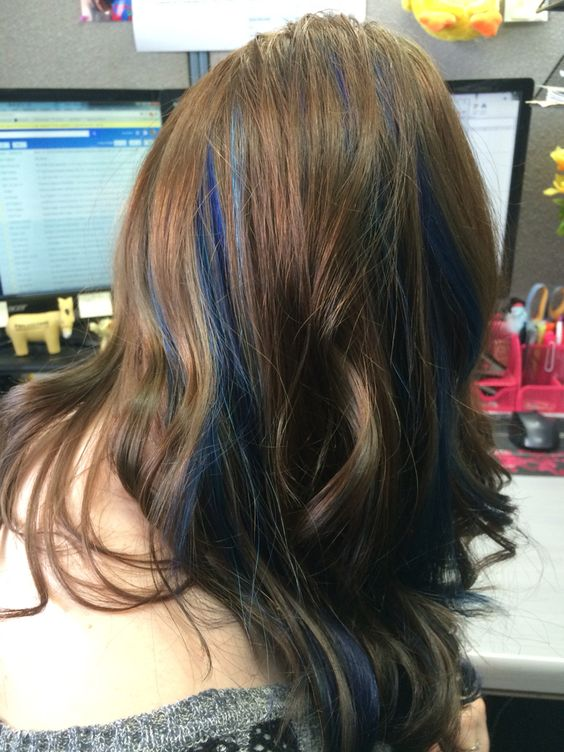 long chestnut wavy hair with deep blue peekaboo highlights that make it playful
