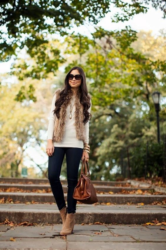navy skinnies, a neutral long sleeve top, beige booties and a brown chunky fur waistcoat