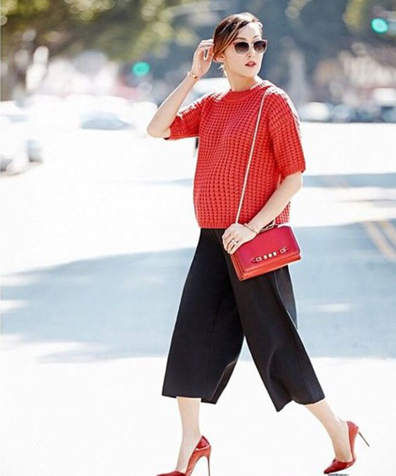 a coral short sleeve sweater, black culottes, a red bag and heels for a bold and bright look
