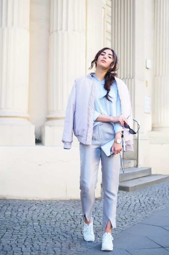 grey pants, a blue shirt, a lavender bomber jacket and white sneakers