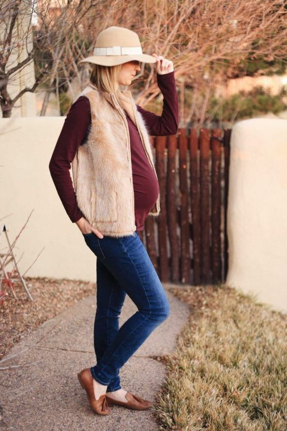 navy skinnies, a burgundy long sleeve top, a faux fur waistcoat, brown moccasins and a neutral hat