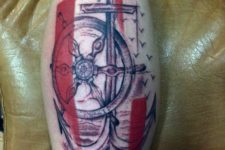 Abstract ship wheel and anchor tattoo on the leg