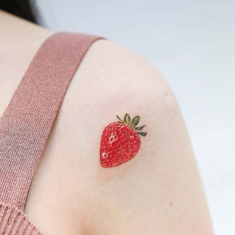 strawberry tattoo on a shoulder