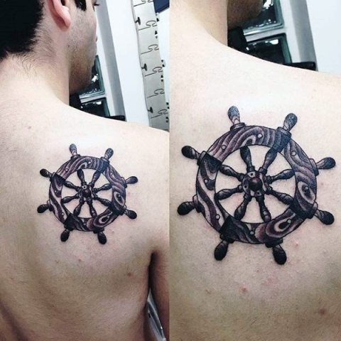 Black and white ship wheel tattoo on the back