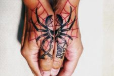 Black spider and red web tattoo on the both hands