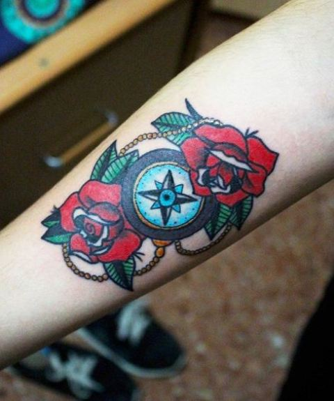 Compass and red flowers tattoo on the forearm