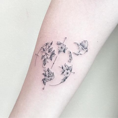 Compass, bird and flowers tattoo on the arm