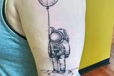 Cool astronaut with balloon tattoo